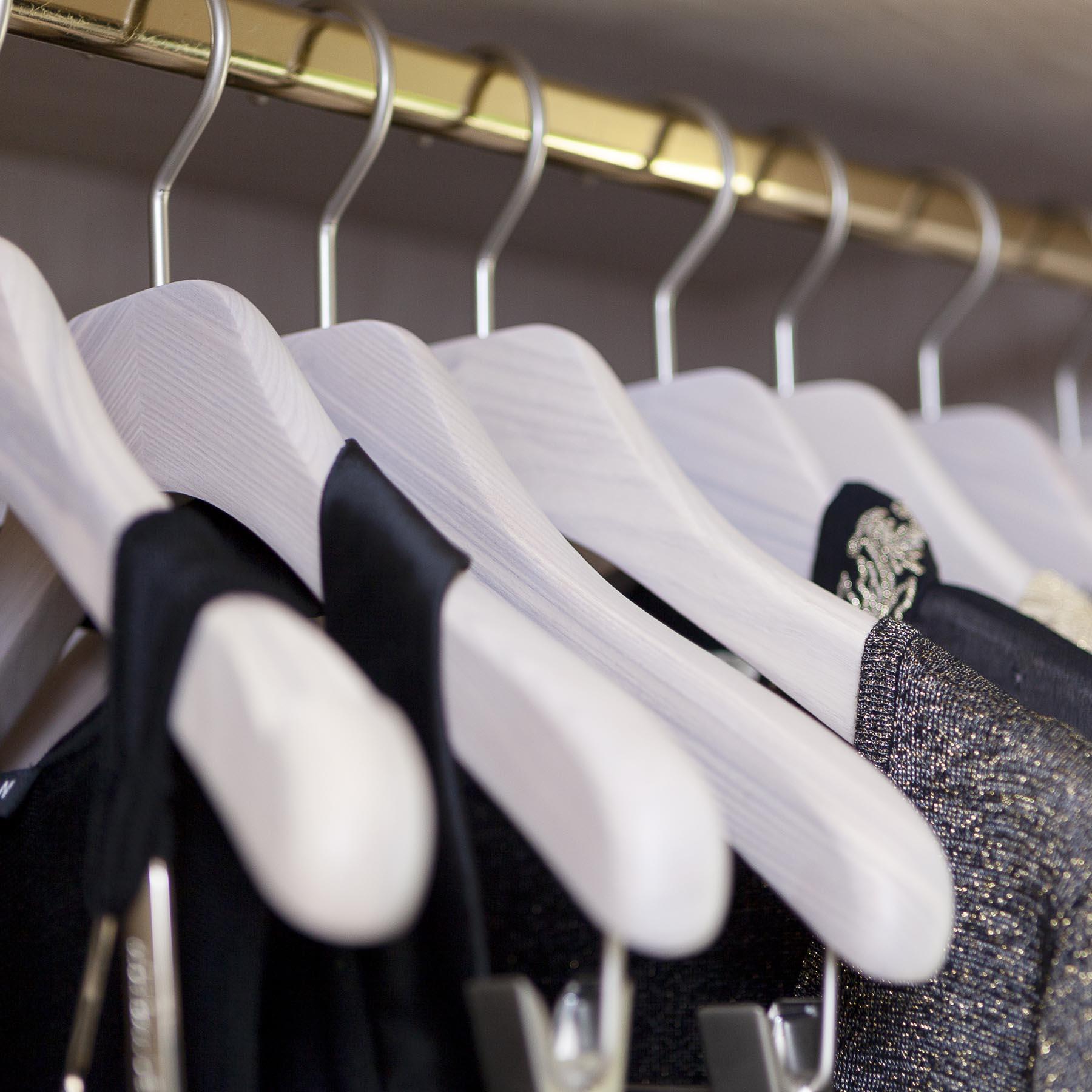 Collection de cintres en bois blanc lasuré pour un dressing haut de gamme